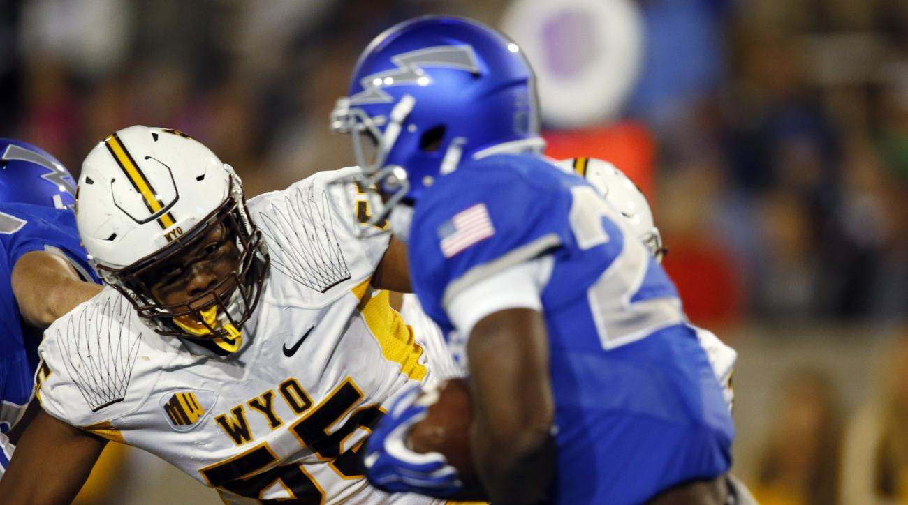 Wyoming defensive end Eddie Yarbrough, back, tackles Air Force running back Jacobi Owens in the first half of an NCAA college football game at Air Force Academy, Colo., Saturday, Oct. 10, 2015. (AP Photo/David Zalubowski)