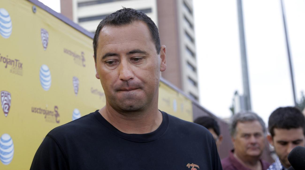 FILE - In this Aug. 25, 2015, file photo, Southern California NCAA college football head coach Steve Sarkisian speaks to members of the media before practice on the campus in Los Angeles. USC fired Sarkisian one day after the troubled coach was put on lea