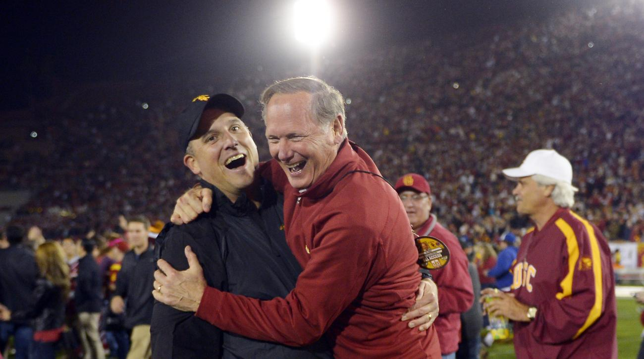FILE - In this Nov. 16, 2013 file photo, Southern California athletic director Pat Haden, right, jumps into the arms of offensive coordinator Clay Helton after USC defeated Stanford in an NCAA college football game in Los Angeles. Helton will assume the U