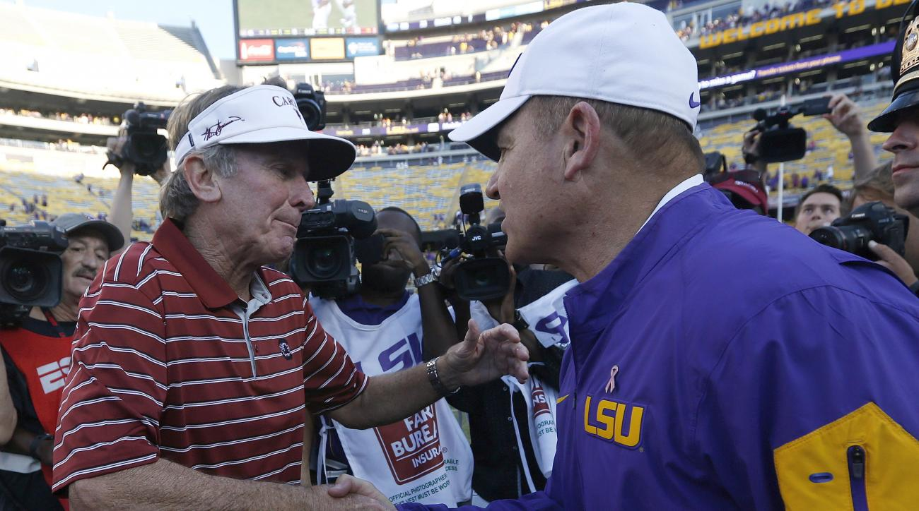 FILE - In this Saturday, Oct. 10, 2015, file photo, South Carolina head coach Steve Spurrier, left, and LSU head coach Les Miles shake hands after an NCAA college football game in Baton Rouge, La. LSU won 45-24. Spurrier is retiring in the middle of his 1