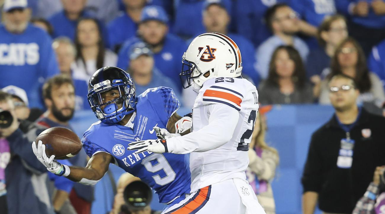 Kentucky wide receiver Garrett Johnson (9) catches a pass in front of Auburn defensive back Johnathan Ford during the first half of an NCAA college football game Thursday, Oct. 15, 2015, in Lexington, Ky. (AP Photo/David Stephenson)