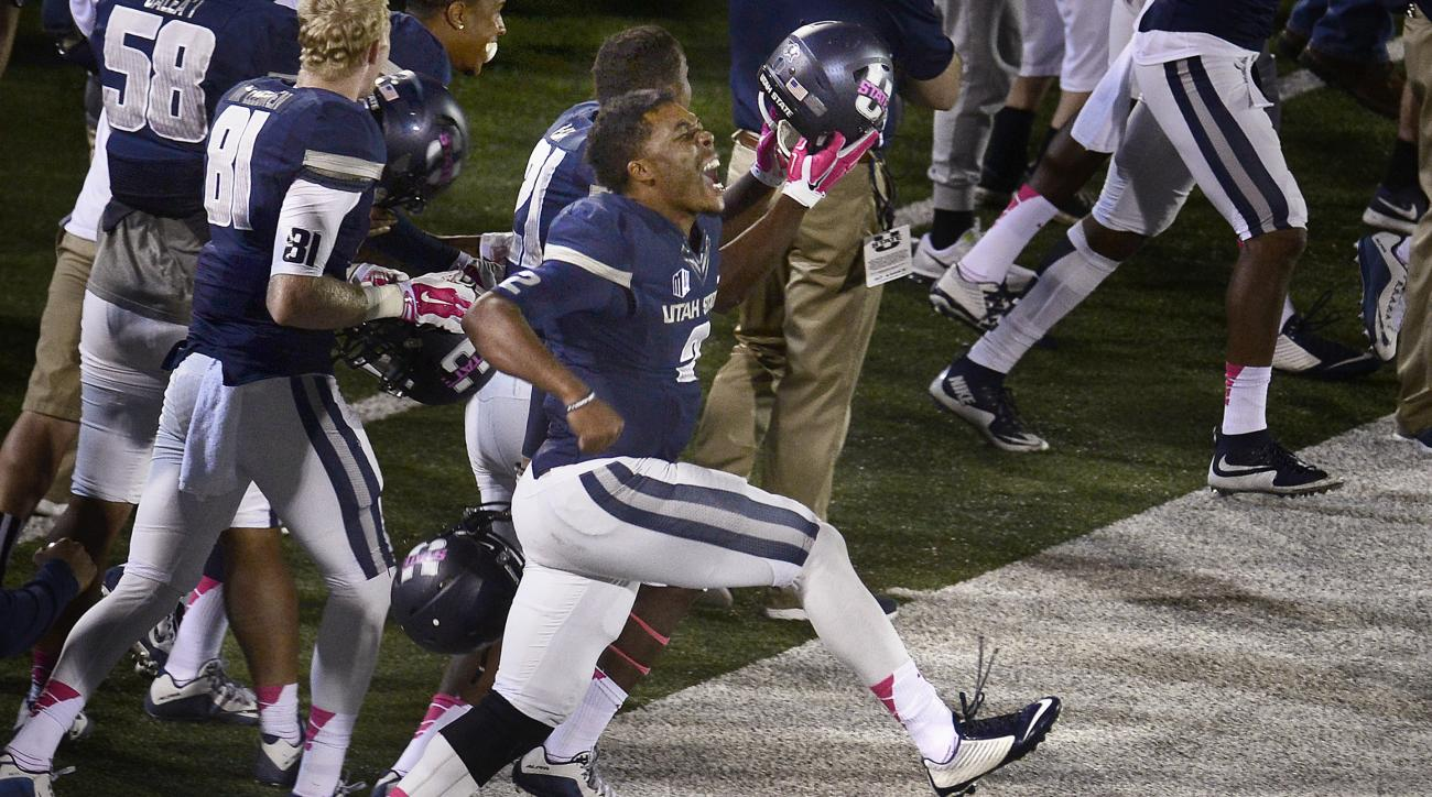 Utah State quarterback Kent Myers (2) leaps and yells after the defense recovered a Boise State fumble late in the first half of an NCAA college football game Friday, Oct. 16, 2015, in Logan, Utah. (Scott Sommerdoft/The Salt Lake Tribune via AP) DESERET N