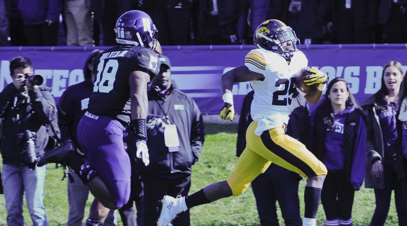 Iowa running back Akrum Wadley (25)  runs for a touchdown against Northwestern  linebacker Anthony Walker (18) during the second quarter of an NCAA college football game in Evanston, Ill.,  on Saturday, Oct. 17, 2015. (AP Photo/Matt Marton)