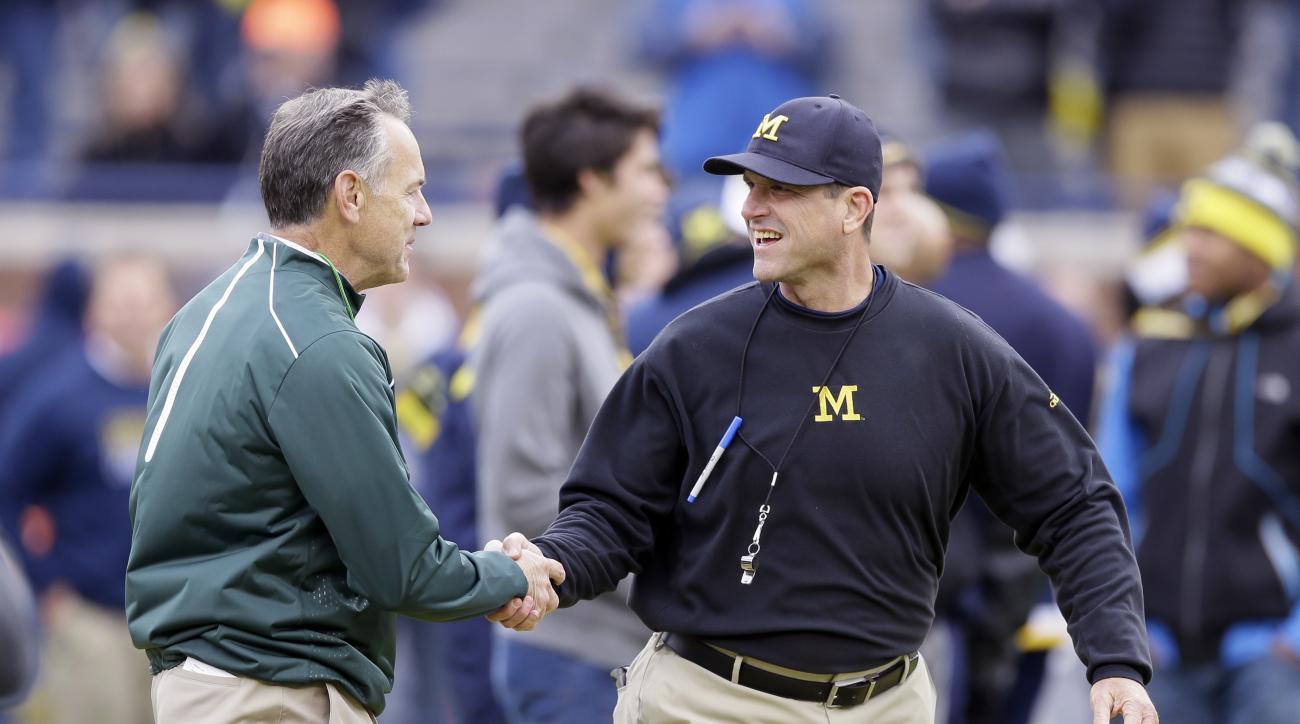 Michigan State head coach Mark Dantonio, left, greets Michigan head coach Jim Harbaugh before an NCAA college football game, Saturday, Oct. 17, 2015, in Ann Arbor, Mich. (AP Photo/Carlos Osorio)