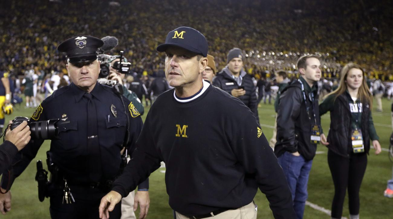Michigan head coach Jim Harbaugh walks off the field after their 27-23 loss to Michigan State in an NCAA college football game, Saturday, Oct. 17, 2015, in Ann Arbor, Mich. (AP Photo/Carlos Osorio)