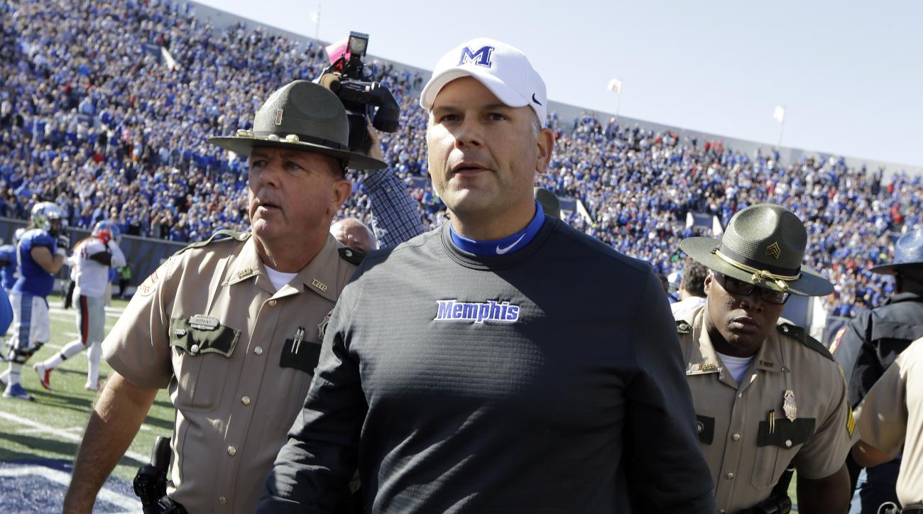 In this Oct. 17, 2015 photo, Memphis head coach Justin Fuente is escorted from the field after beating Mississippi in an NCAA college football game in Memphis, Tenn.  Fuente has turned around a program given up for dead, transforming downtrodden Memphis