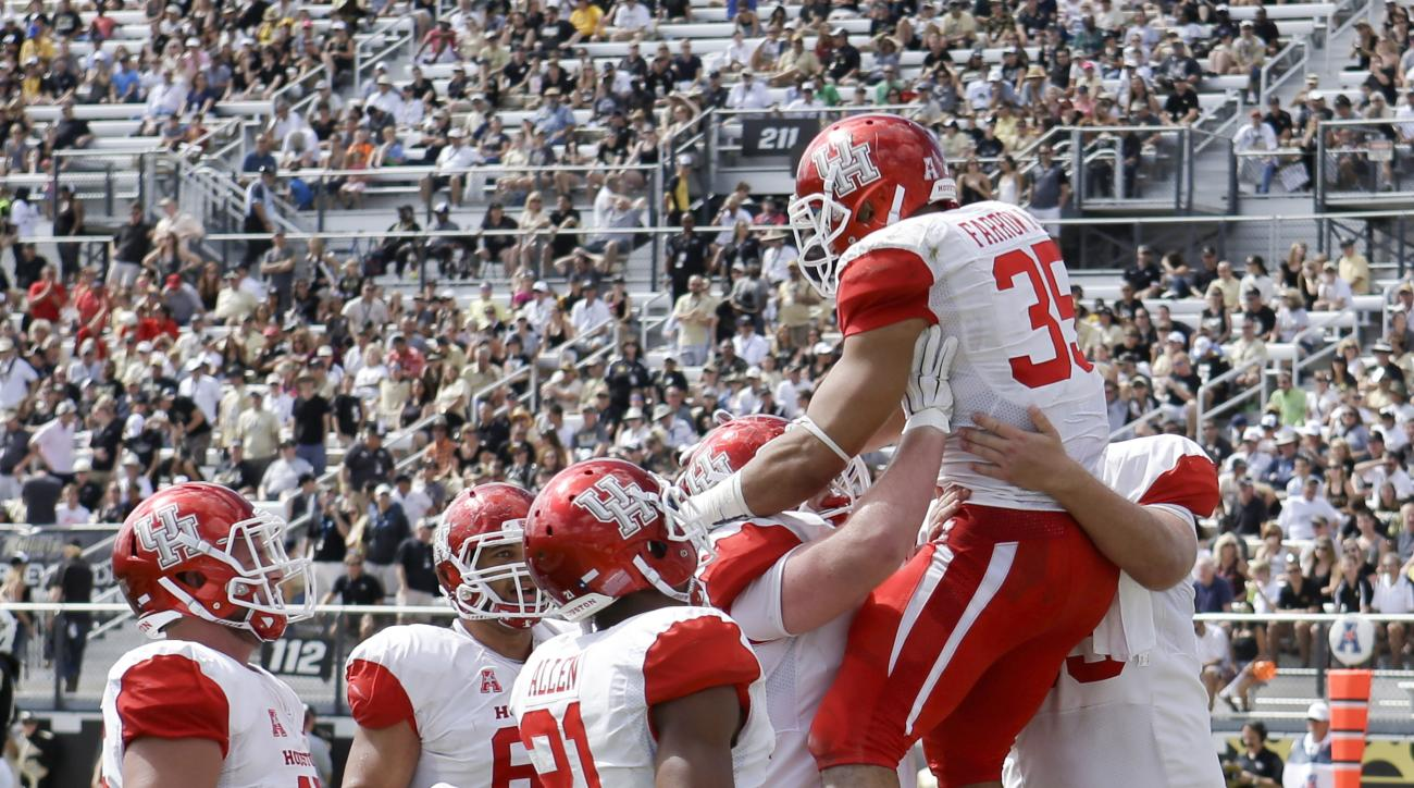 Houston players celebrate with running back Kenneth Farrow (35) after he ran 26-yards for a touchdown against Central Florida during the first half of an NCAA college football game, Saturday, Oct. 24, 2015, in Orlando, Fla. (AP Photo/John Raoux)
