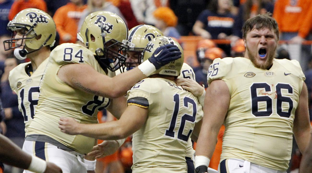 Pittsburgh kicker Chris Blewitt (12) is congratulated by teammates after kicking the game-winning field goal as time expired to defeat Syracuse 23-20 in an NCAA college football game in Syracuse, N.Y., Saturday, Oct. 24, 2015. (AP Photo/Nick Lisi)