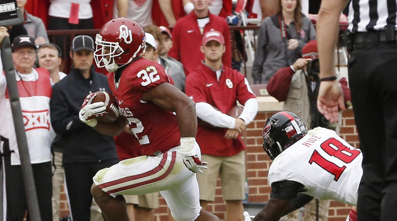 Oklahoma running back Samaje Perine (32) avoids a tackle by Texas Tech linebacker Micah Awe (18) and runs for a touchdown in the second quarter of an NCAA college football game in Norman, Okla., Saturday, Oct. 24, 2015. (AP Photo/Sue Ogrocki)