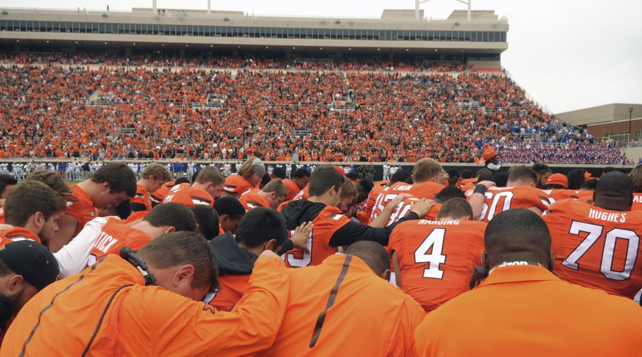 Oklahoma State players and staff form a prayer circle prior to an NCAA college football game between Kansas and Oklahoma St in Stillwater, Okla., Saturday, Oct. 24, 2015. Earlier in the day tragedy struck at the Oklahoma State homecoming parade as a car r