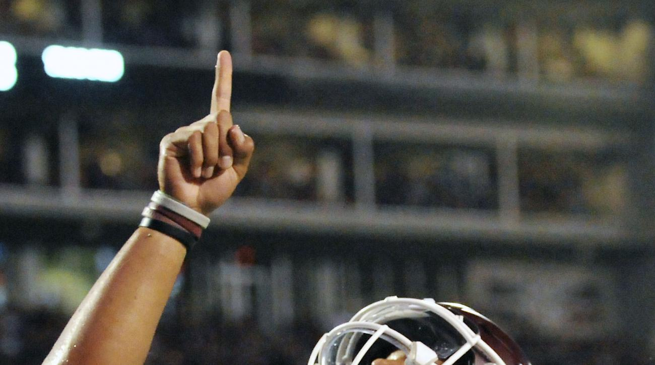 Mississippi State quarterback Dak Prescott (15) points skyward in remembrance of his mother after scoring a touchdown during the first half of an NCAA college football game against Kentucky in Starkville, Miss., Saturday, Oct. 24, 2015. (AP Photo/Jim Lytl