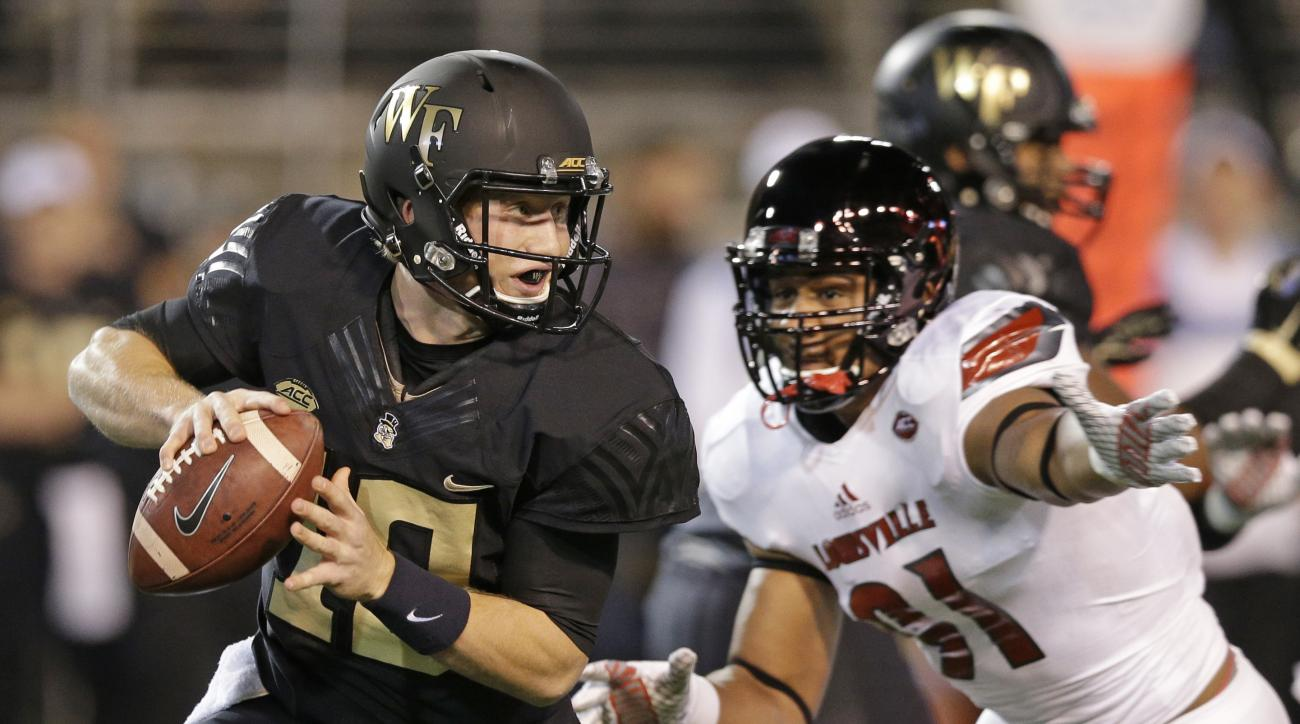 Wake Forest's John Wolford, left, scrambles away from Louisville's Trevon Young, right,  in the first half of an NCAA college football game in Winston-Salem, N.C., Friday, Oct. 30, 2015. (AP Photo/Chuck Burton)