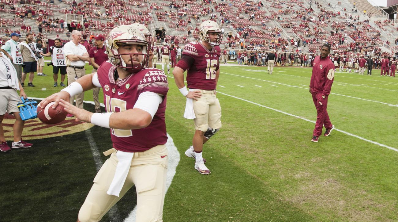 Injured Florida State quarterback Everett Golson, far right, watches as quarterback Sean Maguire warms up prior to an NCAA college football game against Syracuse in Tallahassee, Fla., Saturday, Oct. 31, 2015. (AP Photo/Mark Wallheiser)