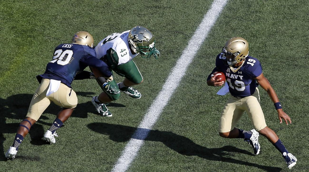 Navy quarterback Keenan Reynolds, right, rushes the ball as teammate Calvin Cass, left, blocks South Florida linebacker Auggie Sanchez in the first half of an NCAA college football game, Saturday, Oct. 31, 2015, in Annapolis, Md. (AP Photo/Patrick Semansk