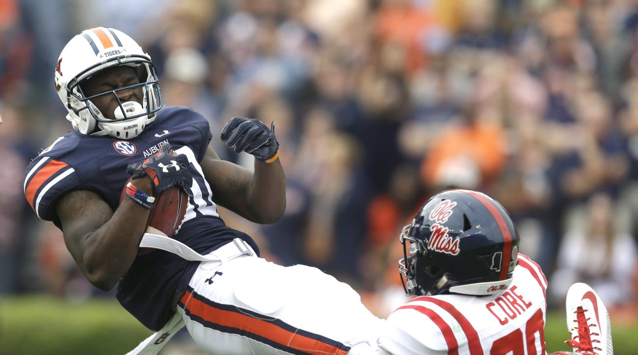 Auburn wide receiver Marcus Davis (80) is tackled by Mississippi's Cody Core (88) during the first half of an NCAA college football game, Saturday, Oct. 31, 2015, in Auburn, Ala. (AP Photo/Butch Dill)