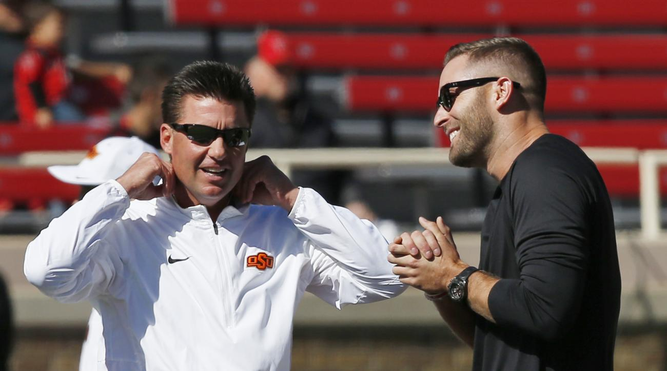 Oklahoma State head coach Mike Gundy, left, talks with Texas Tech head coach Kliff Kingsbury, right, before the start of an NCAA college football game in Lubbock, Texas, Saturday, Oct. 31, 2015. (AP Photo/Sue Ogrocki)