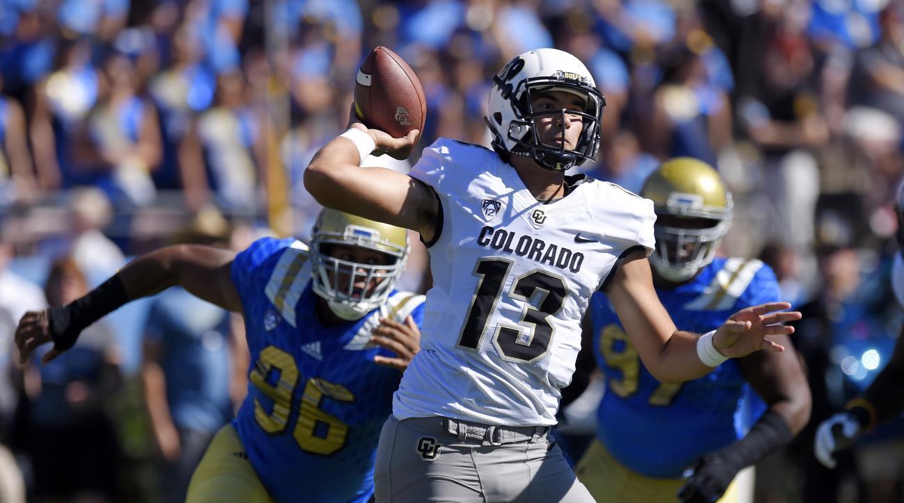 Colorado quarterback Sefo Liufau, center, passes under pressure from UCLA defensive lineman Eli Ankou, left, during the first half of an NCAA college football game, Saturday, Oct. 31, 2015, in Pasadena, Calif. (AP Photo/Mark J. Terrill)