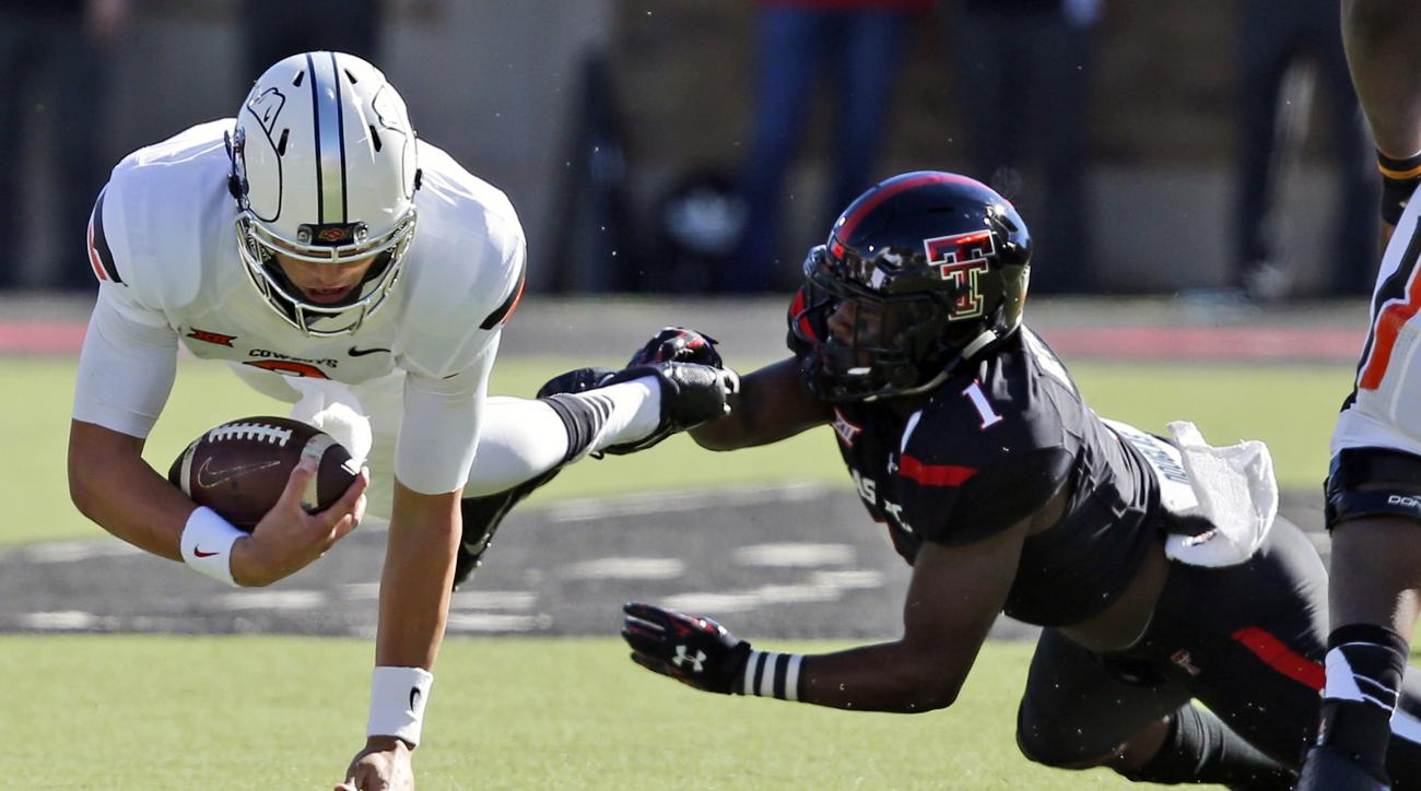 Oklahoma State quarterback Mason Rudolph, left, is tackled by Texas Tech defensive back Nigel Bethel, right, in the second quarter of an NCAA college football game in Lubbock, Texas, Saturday, Oct. 31, 2015. (AP Photo/Sue Ogrocki)