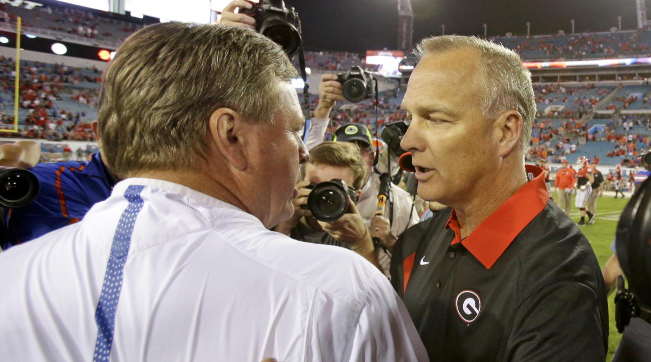 Florida head coach Jim McElwain, left, and Georgia head coach Mark Richt greet each other on the field after an NCAA college football game, Saturday, Oct. 31, 2015, in Jacksonville, Fla.  Florida won 27-3. (AP Photo/John Raoux)