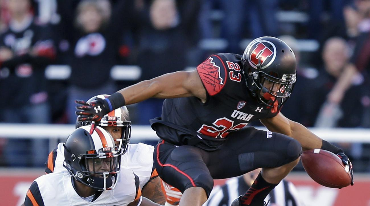 Utah running back Devontae Booker (23) leaps over Oregon State cornerback Dwayne Williams (29) as teammate linebacker Jonathan Willis (32) pursues in the first quarter of an NCAA college football game Saturday, Oct. 31, 2015, in Salt Lake City. (AP Photo/