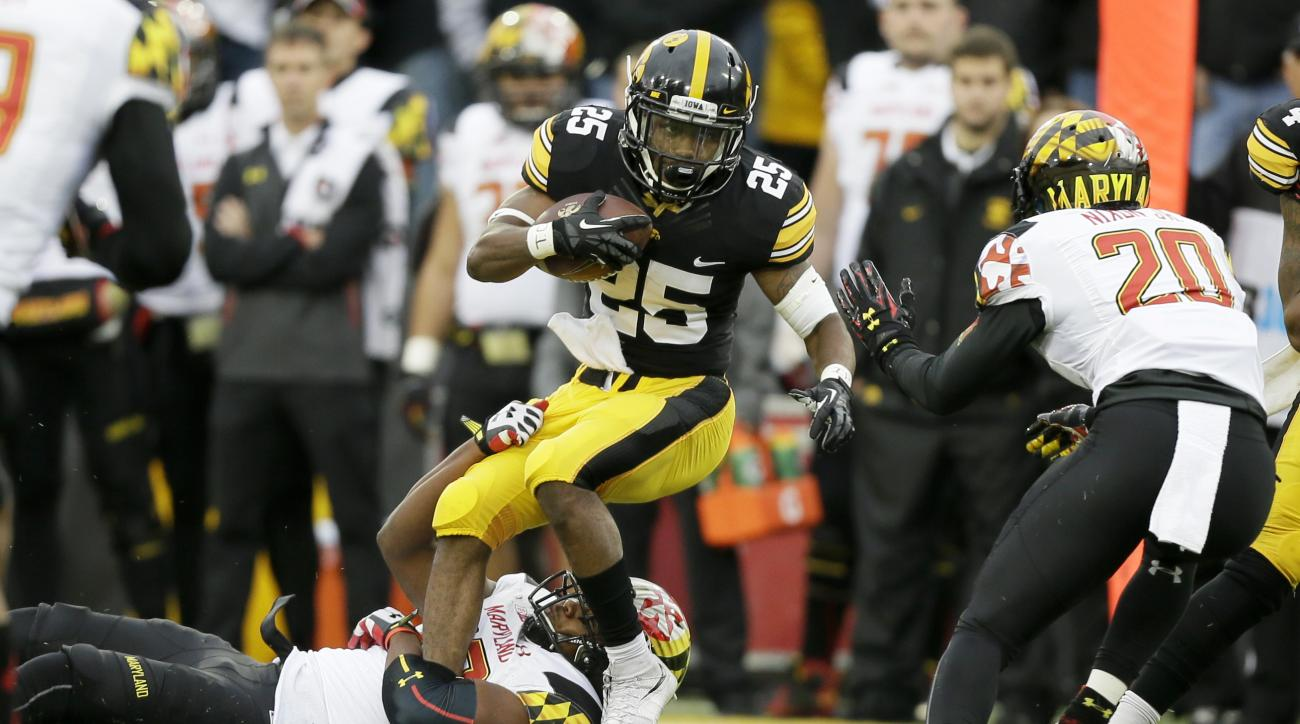 Iowa running back Akrum Wadley (25) tries to break a tackle by Maryland linebacker Jermaine Carter Jr., left, during the first half of an NCAA college football game, Saturday, Oct. 31, 2015, in Iowa City, Iowa. Iowa won 31-15. (AP Photo/Charlie Neibergall