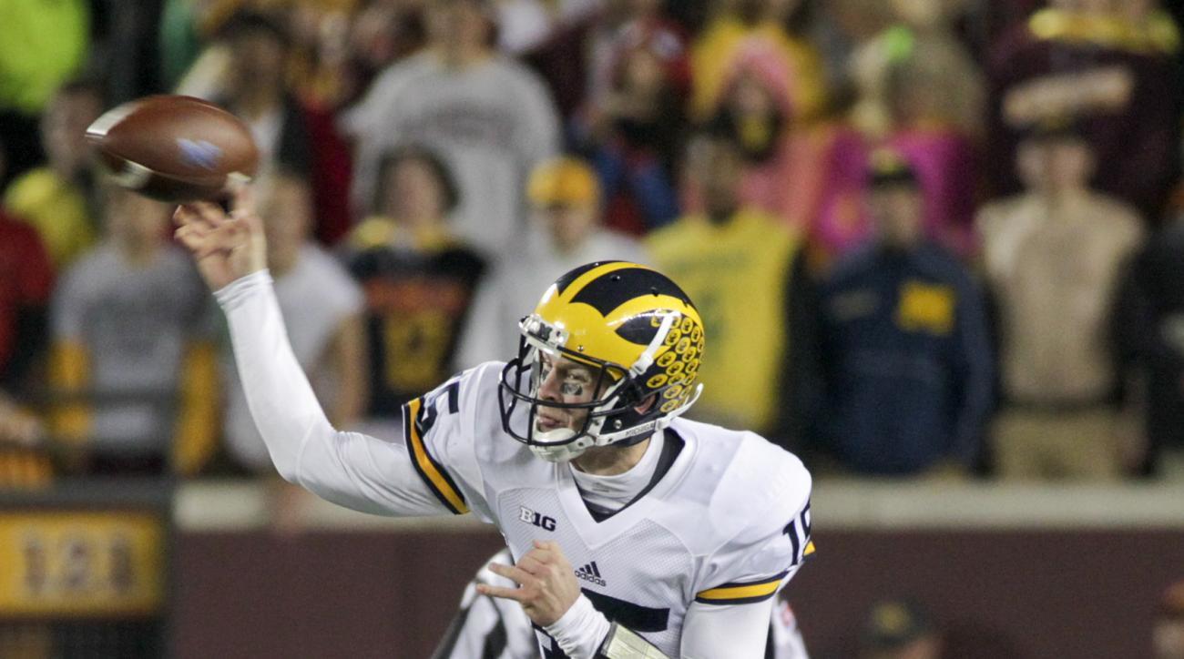 Michigan quarterback Jake Rudock (15) looks to pass during the first half of an NCAA college football game Saturday against Minnesota, Nov. 31, 2015, in Minneapolis.(AP Photo/Paul Battaglia)