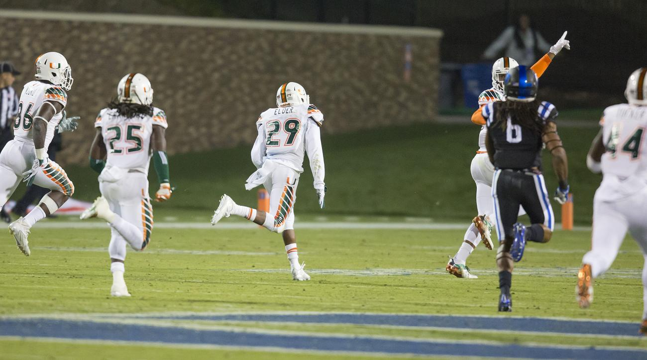 Miami's Corn Elder (29) returns a kickoff,  which featured multiple laterals before Elder subsequently received the final lateral, and scores to beat Duke 30-27 in an NCAA college football game, in Durham, N.C., Saturday, Oct. 31, 2015. (AP Photo/Rob Brow