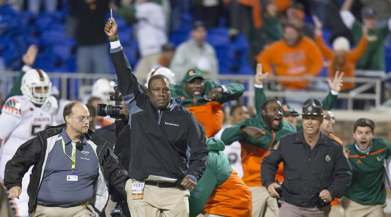 Miami's interim head coach Larry Scott raises his hand after defensive back Corn Elder returned a kickoff, which featured multiple laterals, and scored to defeat Duke 30-27 in an NCAA college football game in Durham, N.C., Saturday, Oct. 31, 2015. (AP Pho