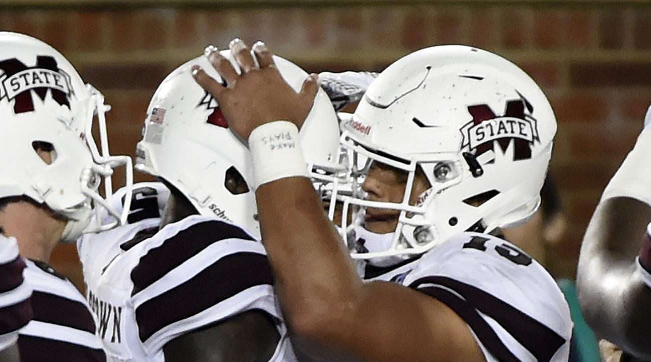 Mississippi State quarterback Dak Prescott, right, and wide receiver Fred Brown celebrate after Brown caught an eight-yard touchdown pass from Prescott during the second half of an NCAA college football game against Missouri on Thursday, Nov. 5, 2015, in