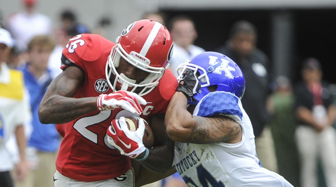 Georgia wide receiver Malcolm Mitchell (26) is tackled by Kentucky cornerback Blake McClain (24) during the second quarter of an NCAA college football game, Saturday, Nov. 7, 2015, in Athens, Ga. (AP Photo/John Amis)