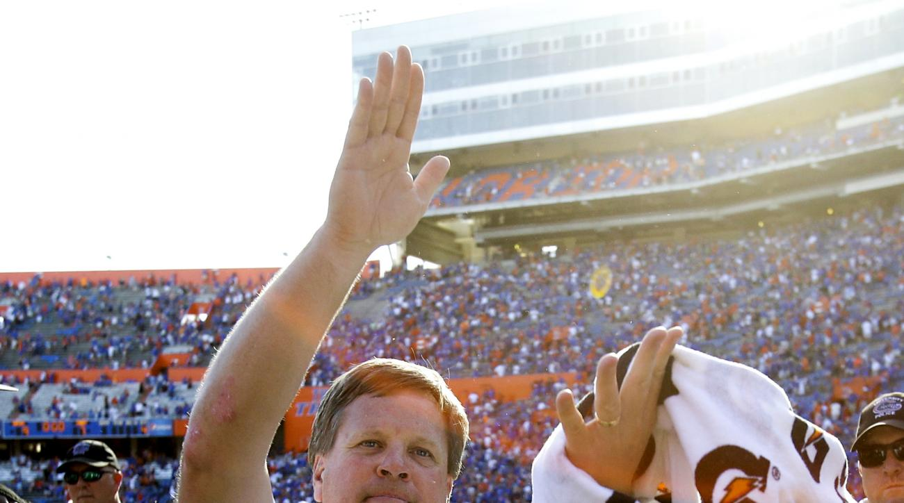Florida head coach Jim McElwain does the gator chomp in front of fans after Florida defeated Vanderbilt 9-7 in an NCAA college football game, Saturday, Nov. 7, 2015, in Gainesville, Fla. (AP Photo/John Raoux)