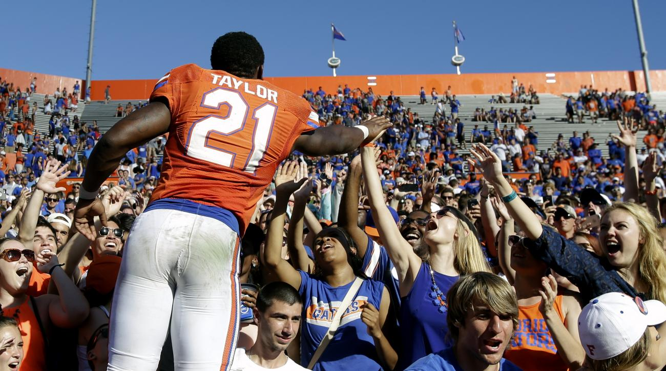 Florida running back Kelvin Taylor (21) high fives fans after an NCAA college football game against Vanderbilt, Saturday, Nov. 7, 2015, in Gainesville, Fla. Florida  won 9-7. (AP Photo/John Raoux)
