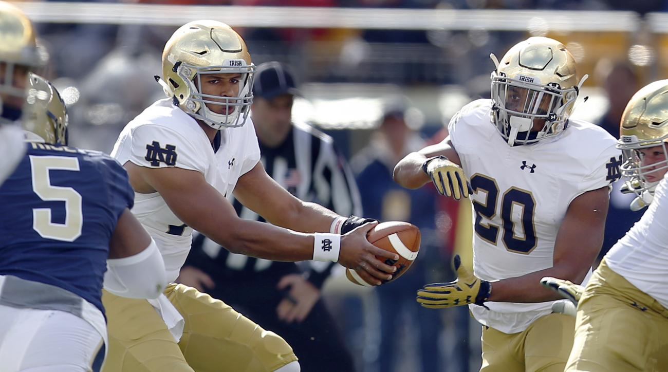 Notre Dame running back C.J. Prosise (20) takes a handoff from quarterback DeShone Kizer (14) as Pittsburgh defensive lineman Ejuan Price (5) pursues in the first quarter of an NCAA football game, Saturday, Nov. 7, 2015 in Pittsburgh. Prosise was injured