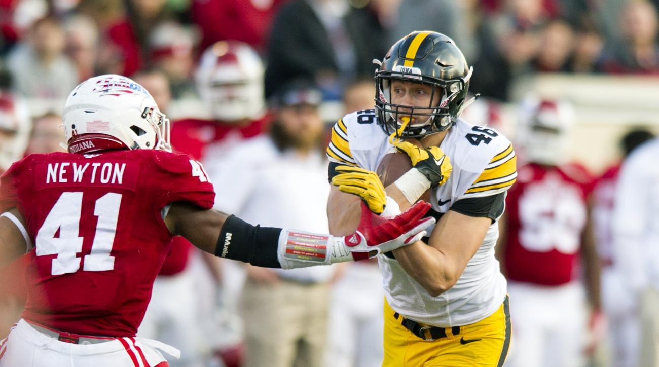 Iowa tight end George Kittle (46) holds onto the ball as he tries to elude the tackling effort to Indiana linebacker Clyde Newton (41) during the first half of an NCAA college football game in Bloomington, Ind., Saturday, Nov. 7, 2015. (AP Photo/Doug McSc