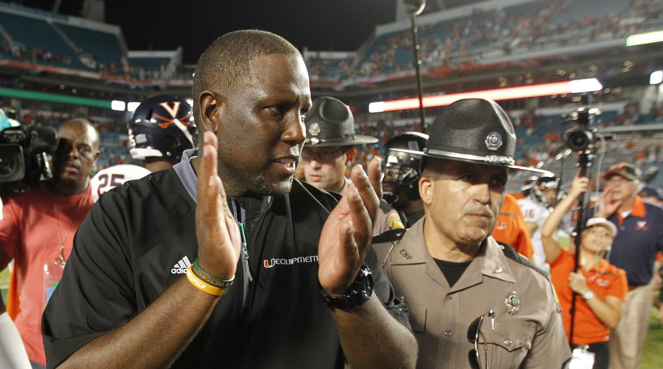 Interim Miami head coach Larry Scott celebrates with his team after they defeated Virginia 27-21 in an NCAA college football game, Saturday, Nov. 7, 2015, in Miami Gardens, Fla. (AP Photo/Joe Skipper)