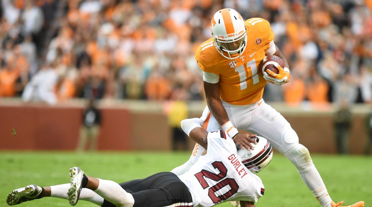 Tennessee quarterback Joshua Dobbs (11) pushes off South Carolina's T.J. Gurley (20) during the first half of an NCAA college football game at Neyland Stadium in Knoxville, Tenn. on Saturday, Nov. 7, 2015. (Adam Lau/Knoxville News Sentinel via AP)