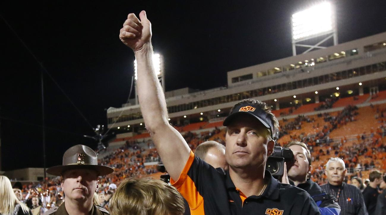 Oklahoma State head coach Mike Gundy, right, gestures to fans as he walks off the field with his son Gage Gundy, left, following a victory over TCU in an NCAA college football game in Stillwater, Okla., Saturday, Nov. 7, 2015. Oklahoma State won 49-29. (A