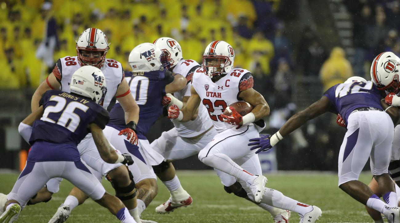 Utah running back Devontae Booker (23) runs toward Washington defensive back Sidney Jones (26) during the first half of an NCAA college football game, Saturday, Nov. 7, 2015, in Seattle. (AP Photo/Ted S. Warren)