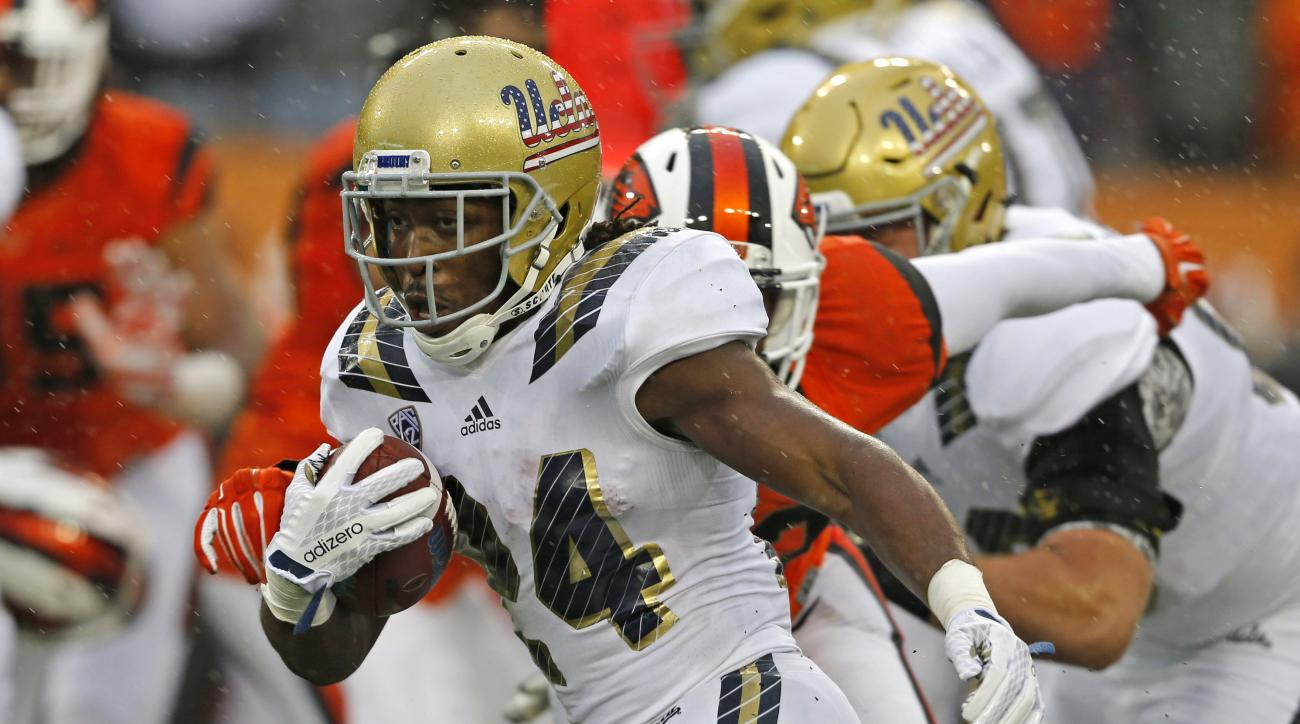 UCLA's Paul Perkins, breaks through the Oregon State defense in the second half of an NCAA football game, in Corvallis, Ore., on Saturday, Nov. 7, 2015. UCLA won 41-0. (AP Photo/Timothy J. Gonzalez)