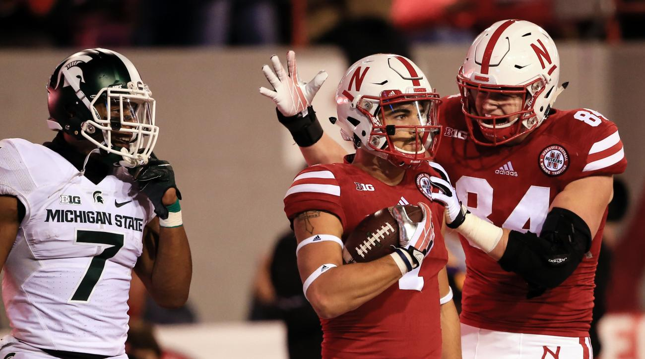 Nebraska wide receiver Jordan Westerkamp, center, is congratulated by teammate tight end Sam Cotton (84) after catching a touchdown pass as Michigan State defensive back Demetrious Cox (7) watches during the first half of an NCAA college football game in