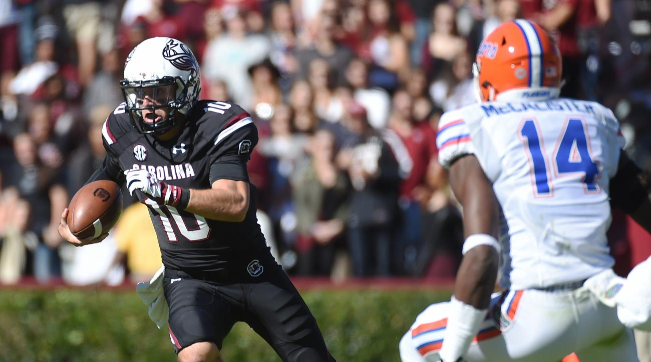 South Carolina quarterback Perry Orth (10) runs for yardage as Florida defensive lineman Alex McCalister (14) defends during the first half of an NCAA college football game, Saturday, Nov. 14, 2015, in Columbia, S.C. (AP Photo/Rainier Ehrhardt)