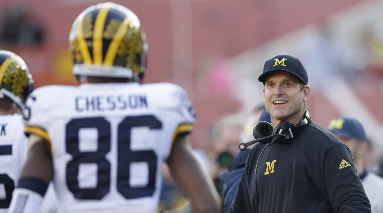 Michigan head coach Jim Harbaugh congratulates Jehu Chesson (86) after Chesson caught a touchdown pass during the first half of an NCAA college football game against Indiana, Saturday, Nov. 14, 2015, in Bloomington, Ind. (AP Photo/Darron Cummings)
