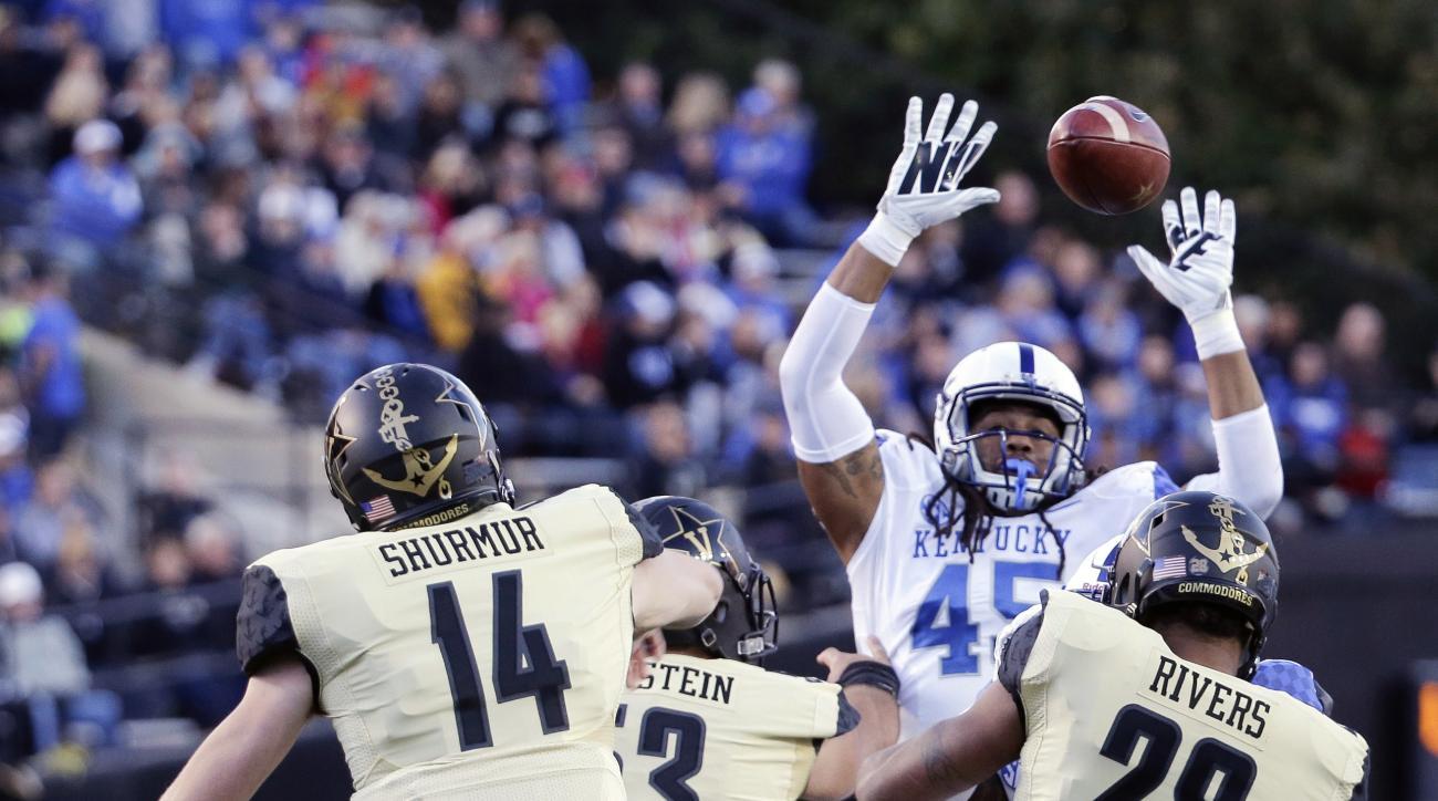 Vanderbilt quarterback Kyle Shurmur (14) passes over the reach of Kentucky linebacker Josh Forrest (45) in the first half of an NCAA college football game Saturday, Nov. 14, 2015, in Nashville, Tenn. (AP Photo/Mark Humphrey)