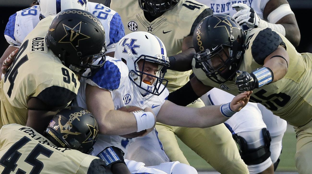 Kentucky quarterback Drew Barker, center, is brought down for a 1-yard loss by a group of Vanderbilt defenders in the first half of an NCAA college football game Saturday, Nov. 14, 2015, in Nashville, Tenn. (AP Photo/Mark Humphrey)