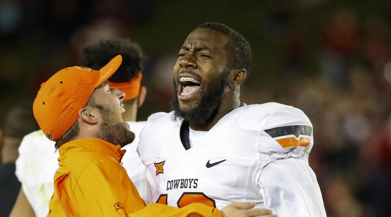 Oklahoma State linebacker Kirk Tucker, right, celebrates with a coach after they stopped Iowa State on a fourth-down play late during the second half of an NCAA college football game, Saturday, Nov. 14, 2015, in Ames, Iowa. (AP Photo/Justin Hayworth)