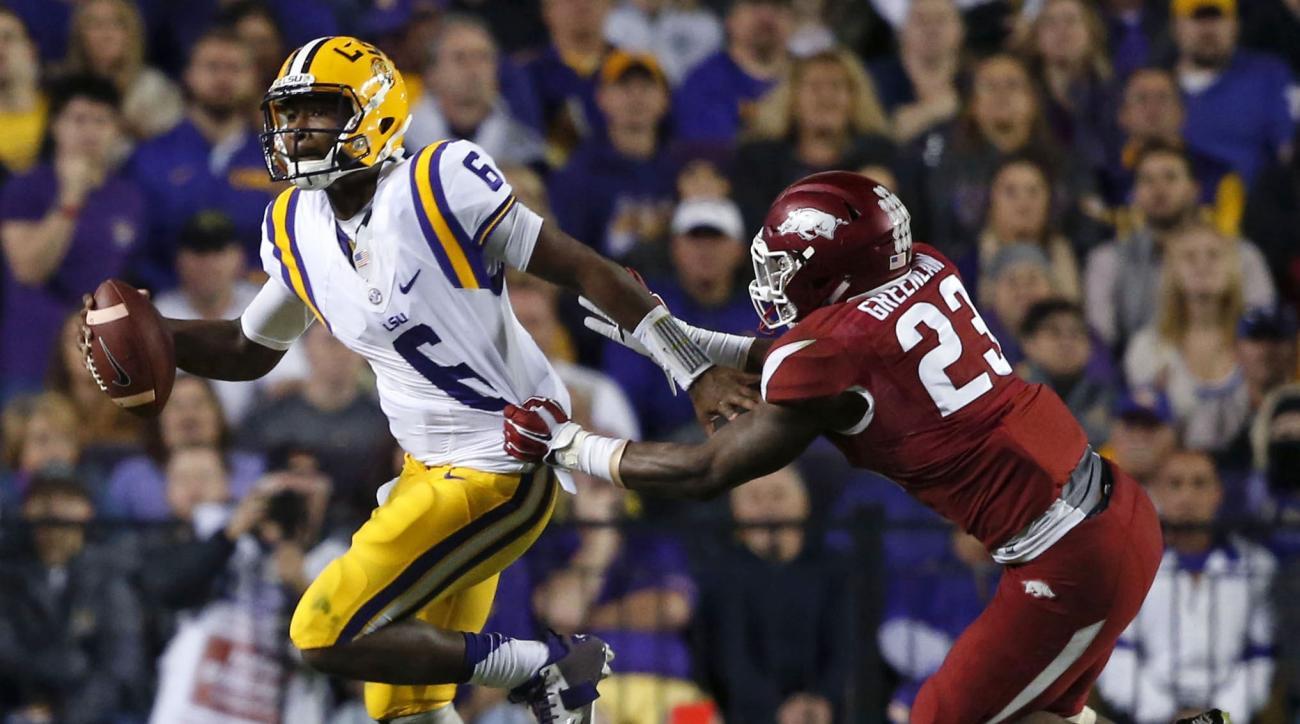 LSU quarterback Brandon Harris (6) scrambles to avoid Arkansas linebacker Dre Greenlaw (23) in the first half of an NCAA college football game in Baton Rouge, La., Saturday, Nov. 14, 2015. Harris fumbled on the play setting up an Arkansas touchdown.  (AP