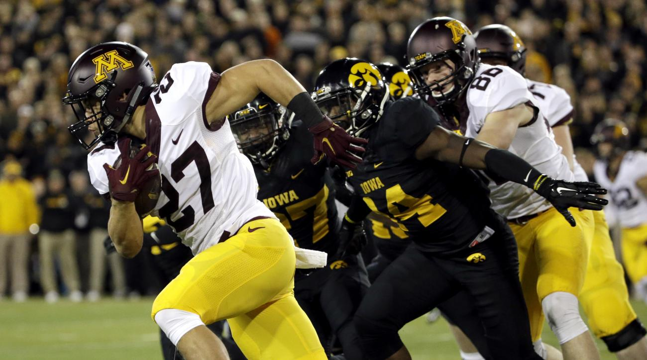 Minnesota inning back Shannon Brooks (27) runs with the ball against Iowa defensive back Jordan Lomax (27) and defensive back Desmond King (14) during the first half of an NCAA college football game, Saturday, Nov. 14, 2015, in Iowa City, Iowa.  (AP Photo