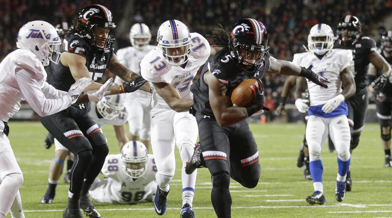 Cincinnati running back Mike Boone (5) scores a touchdown on a run against Tulsa safety Jordan Mitchell (13) the first half of an NCAA college football game, Saturday, Nov. 14, 2015, in Cincinnati. (AP Photo/John Minchillo)