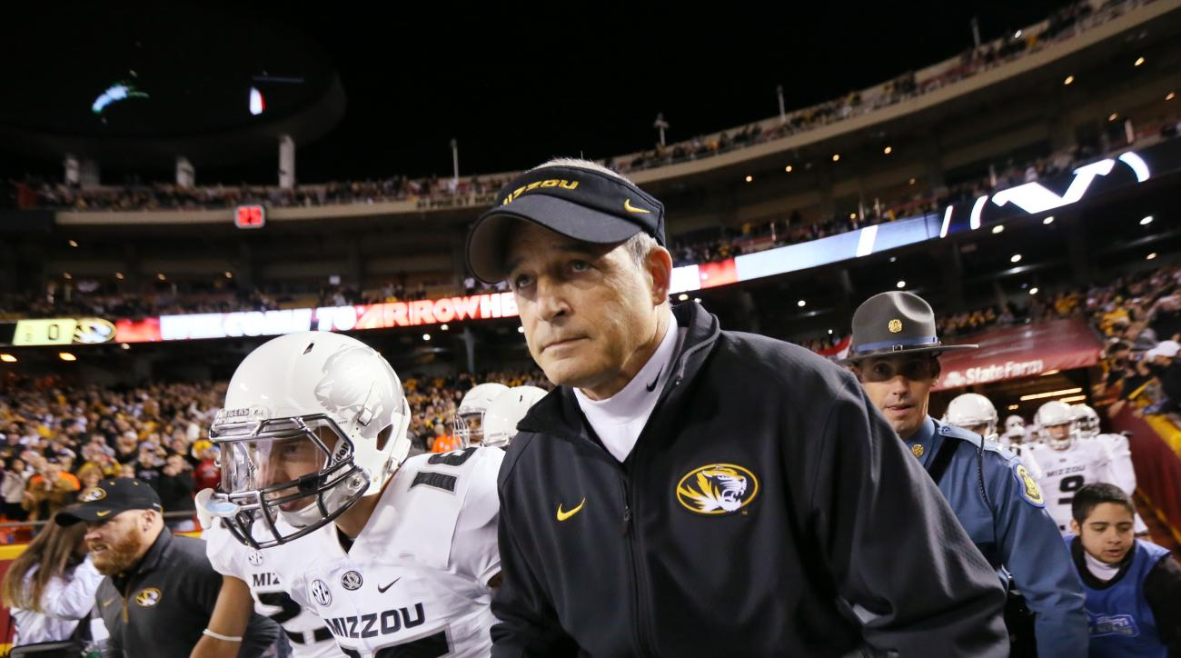 Missouri head coach Gary Pinkel, second from right, leads his players onto the field before an NCAA football game between Missouri and BYU on Saturday, Nov. 14, 2015, at Arrowhead Stadium in Independence, Mo. Pinkel announced Friday he is stepping down at
