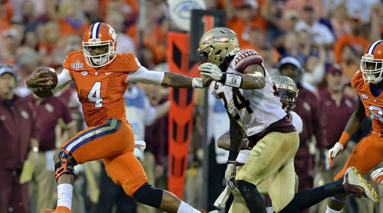 FILE - In this Nov. 7, 2015, file photo, Clemson quarterback Deshaun Watson (4) fends off Florida State's Terrance Smith to gain a first down during the first half of an NCAA college football game in Clemson, S.C. In the year of the running back, Watson i